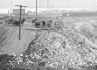 Garbage dump west of Westlake Avenue near South Lake Union, 1915. Looking northeast toward Capitol Hill. Horse-drawn wagons dumped garbage in low areas to create usable land alongside waterways. Courtesy Seattle Municipal Archives, Item No. 867.